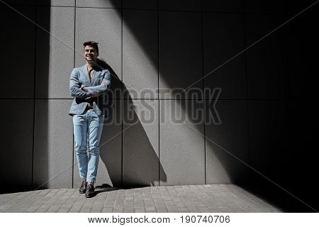 Joyful man is leaning against wall and looking ahead with light smile. He crossing hands. Copy space on right side