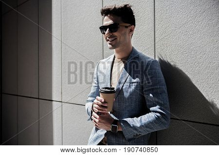 Happy man wearing sunglasses is holding beverage and looking ahead with smile. He leaning against grey wall. Portrait