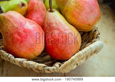 Colorful ripe fresh organic pears in wicker basket on aged wood kitchen table near window natural light healthy diet rural countryside style top view