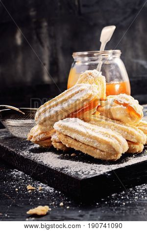 Shortbread butter cookies with apricot jam on black wooden background with free text space. Selective focus.