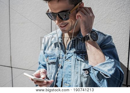 Hilarious male person is putting earphone into ear and looking at screen of phone with wide smile. He wearing sunglasses
