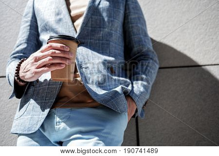 Stylish man is holding cup of beverage. He leaning against grey wall. Low angle. Close up of hands