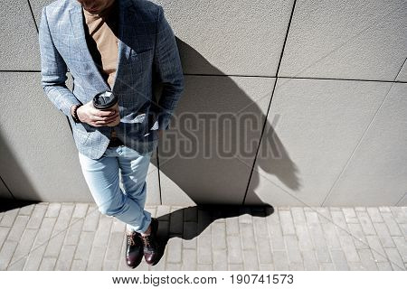 Active man is leaning against grey wall and holding cup of beverage. Top view. Copy space on right side