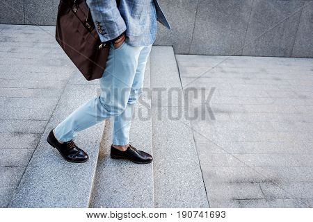 Elegant man is putting hands at pockets and walking down stairs outside. Copy space on right side. Focus on legs