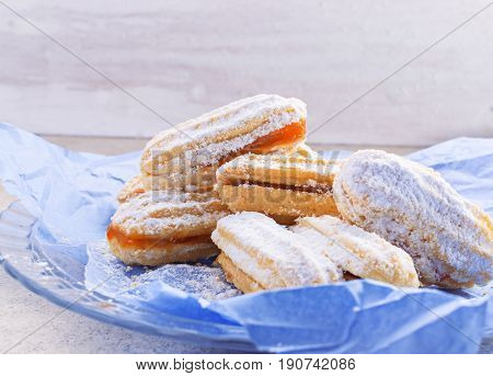 Shortbread butter cookies with apricot jam on light wooden background with free text space. Selective focus.