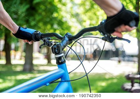 Man is getting ready for bike trip. Close up of male hands on handlebars