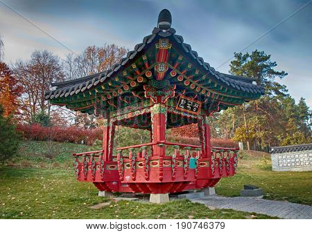Ornate chinese pavilion in autumn park, dramatic sky