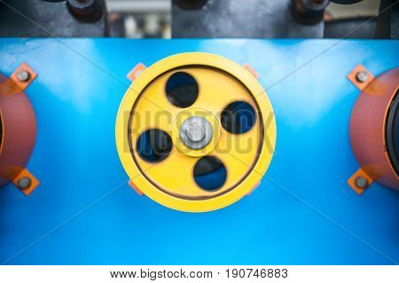 Rotating wheels of a winding machine. Rotating wheel close-up. Yellow wheel on a blue background.