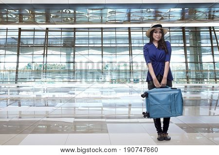 Smiling Asian Woman Traveller With Hat Carrying Luggage