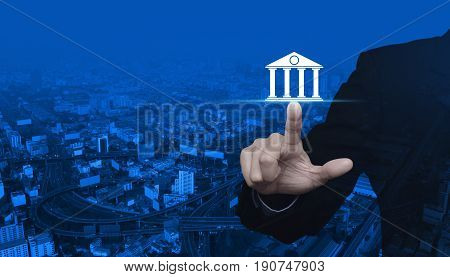 Businessman pressing bank icon over modern city tower street and expressway Business banking concept