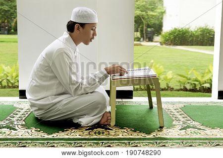Side View Of Asian Muslim Man Reading Holy Book Koran