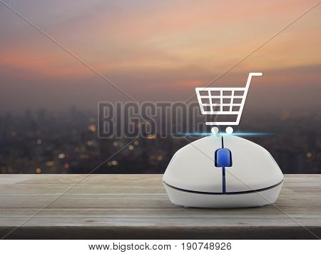 Shopping basket icon with wireless computer mouse on wooden table over blur of cityscape on warm light sundown Shop online concept