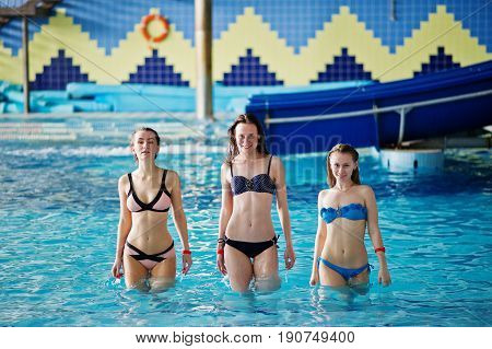Three stunning girls in bikini walking out of the pool in the water park.