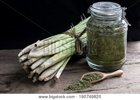 Lemon Grass (Cymbopogon citratus) and Dried lemongrass in glass bottles on wood table.