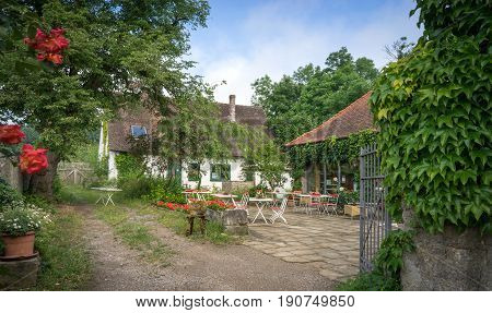 Bavarian backyard with sitting accommodation between overgrown plants