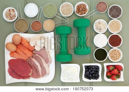 Super food for body builders with dumbbells, meat, fish, fruit, dairy, dietary supplement powders, grains, cereals, pulses, seed and herbs on green wood background.