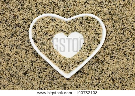 Hulled hemp seed super food in a heart shaped bowl.