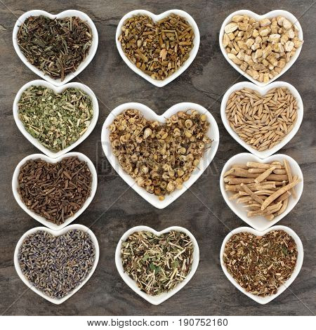 Herb selection used in herbal medicine for anxiety and sleeping disorders in white china heart shaped dishes.