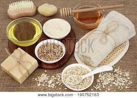 Skincare and body care products to cleanse and soothe skin disorders with oats, honey, oil, natural moisturizer and soap on burlap background.