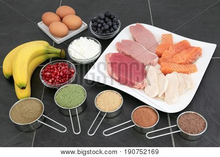 Health food for body builders with lean meat, salmon, dairy, fruit and nutritional supplement powders on slate background.