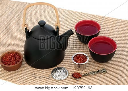 Safflower herb tea with oriental teapot and cups with strainer and old spoon on bamboo over white background. Used also in chinese herbal medicine.