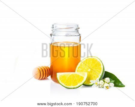 honey in glass jar wooden honey dipper and fresh limes with leaf and flowers on white background with room for copy space