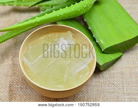 aloe vera gel in wooden bowl and leaf on rustic fabric background