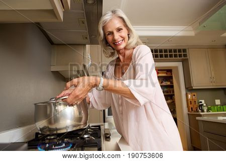 Smiling Older Lady Lifting Pot From Stove