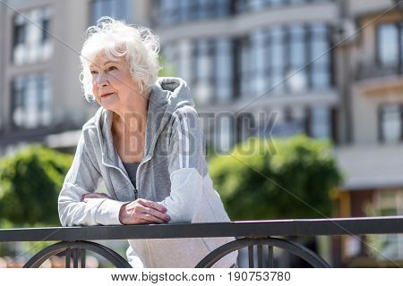 Happy elderly good-looking woman wearing sports wear is leaning on metal city fence. Copy space in right place