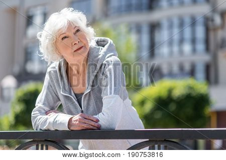 Waist up portrait of old thoughtful lady having break time while jogging down city streets. She is leaning on metal fence and looking to sunny sky