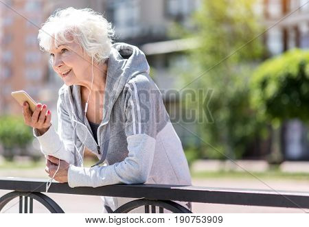 Jolly aged lady is talking with her friend via smart phone, leaning on fence and looking somewhere to distance. She is having sportswear on. Copy space in right side