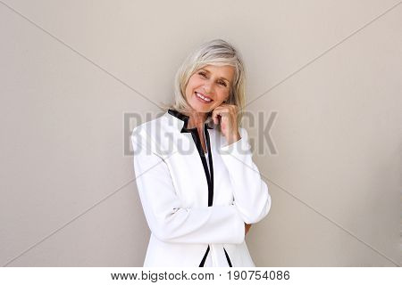 Smiling Older Business Woman Standing Against Wall