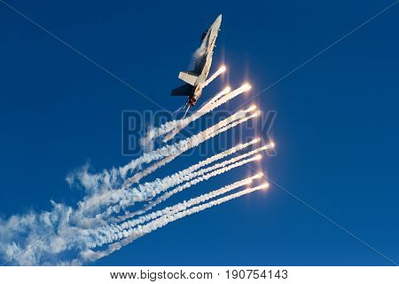 HELSINKI, FINLAND - JUNE 9, 2015: Finnish Air Force Hornet F/A-18 shooting out flares at the Kaivopuisto Air Show June 9, 2017 in Helsinki, Finland.