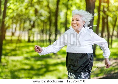 Waist up portrait of merry old lady running through park avenue. She is smiling and enjoying her sport activities