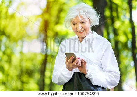 Waist up portrait of merry old woman texting via her smart phone. She is looking at phone screen and smiling
