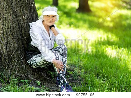 Full length portrait of senior lady relaxing in summer park after doing exercise. She is sitting under old big tree and smiling