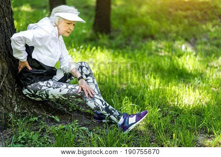Worn-out senior lady is sitting on large tree roots and relaxing after exercise. She is touching her back as if having pain there. Copy space in right side