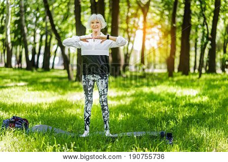 Full length portrait of cheerful old lady doing yoga in forest. She is standing straight barefoot on mat and warming up