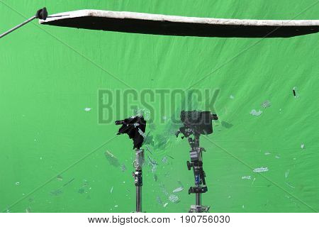 Implosion of a glass of an car on a background of a green sheet for a scene of an action movie