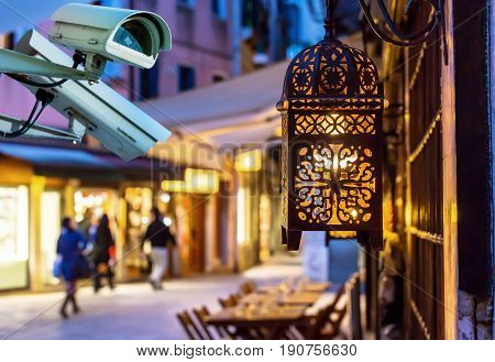 Security Cctv Camera With Touristic Street By Night On Blurry Background