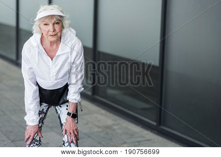 Portrait of pensive old lady resting while training near new city building. She is standing on half bent legs and leaning on her laps. Copy space in right side