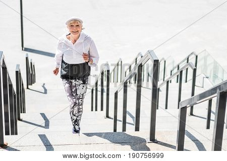 Portrait of happy old woman raising upstairs. She is jogging on city ladder construction and smiling