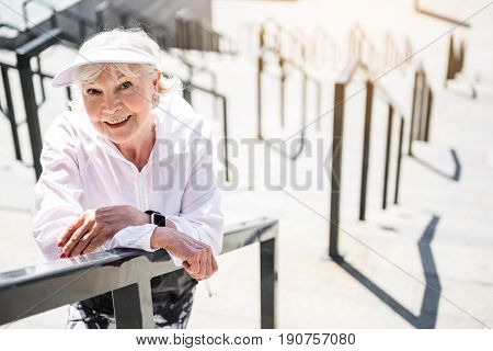 Waist up portrait of happy old lady standing on top of city stairs outside building. She is leaning on metal handrails by hands and smiling. Copy space in right side