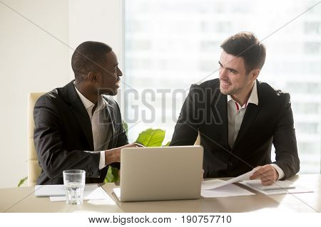 Two accomplished multiracial businessmen discussing idea new business projects at office desk, multi ethnic business group having pleasant funny conversation indoors, running company together