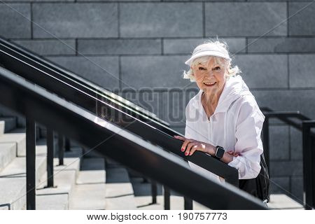 Waist up portrait of happy old lady going upstairs outdoor. She is stopping for a while to rest and holding guard rails by hands. Focus on rails