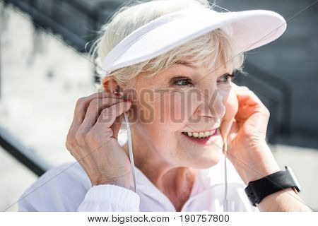 Close up of head of happy old woman listening to music via headphones while training. Focus on earphones, smart watch and hat