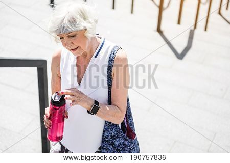 Happy old woman is going to drink water while climbing upstairs from her sports bottle. She is standing near metal rails of stairs and opening bottle. Copy space in right side