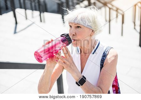 Tired aged woman is standing on top steps of big ladder construction and drinking water from her bottle. Focus on water bottle and smart watch