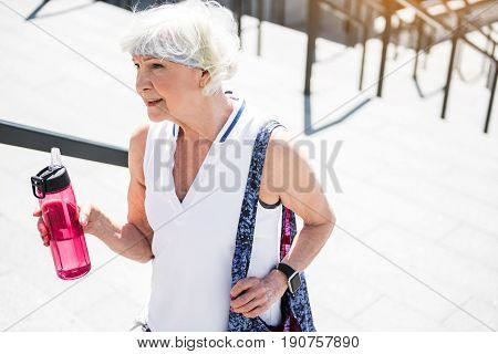 Exhausted elderly woman is climbing slowly upstairs. She is holding bottle of water in one hand. Copy space in right side