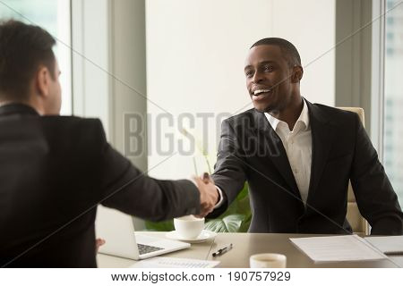 Two multicultural businessmen handshaking over desk, attractive african entrepreneur shaking hand of caucasian client, start finish negotiations, establishing multi-ethnic partnership, making deal